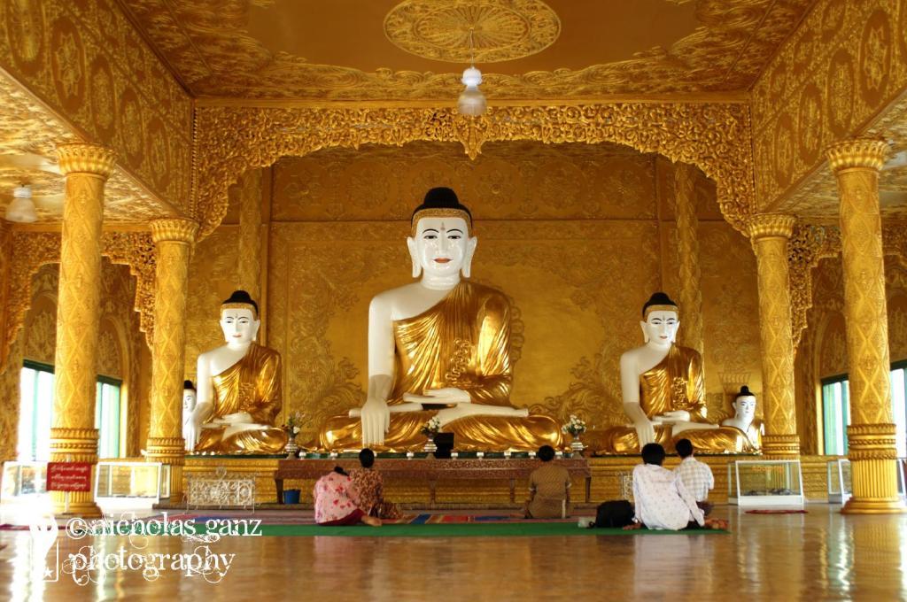 Betende Gläubige vor den Buddha Statuen in der Shwemkhtaw Pagode in Pathein/Bassein.